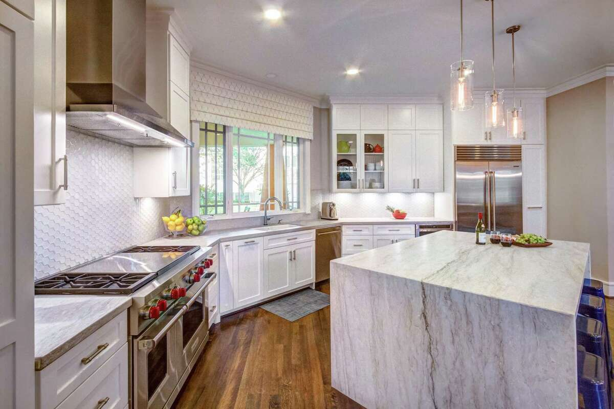 After: Cabinets are more functional and the bigger island is draped in quartzite.