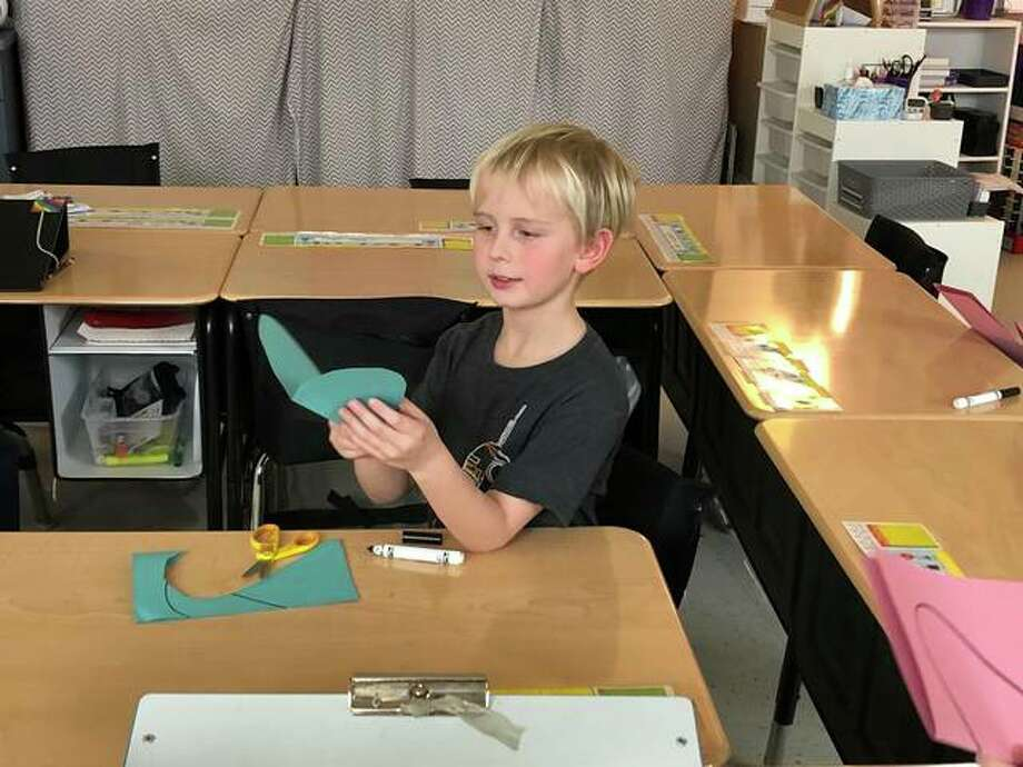 Student Ben Schuenke creates a heart by cutting construction paper during a lesson at Glen Carbon Elementary last week. Photo: Julia Biggs | The Intelligencer