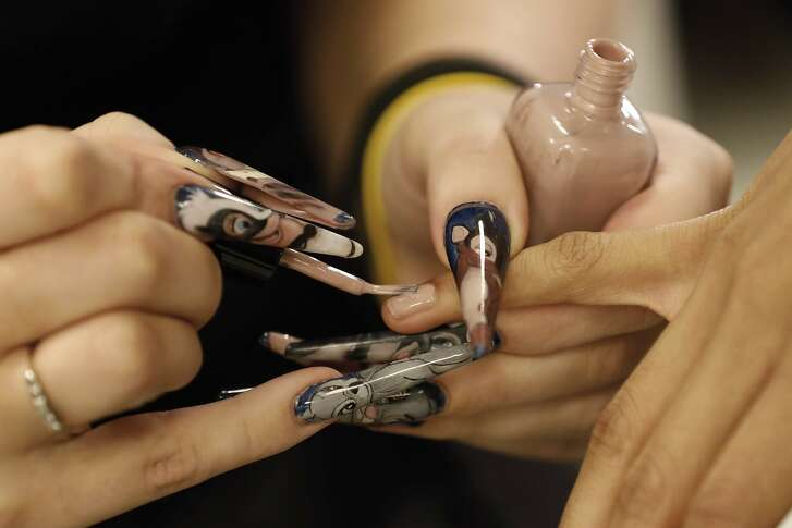 A manicurist wears cartoon-themed nails as she applies nail polish backstage to a model before the Carolina Herrera collection is modeled during Fashion Week in New York, Monday, Feb. 11, 2019. (AP Photo/Richard Drew)