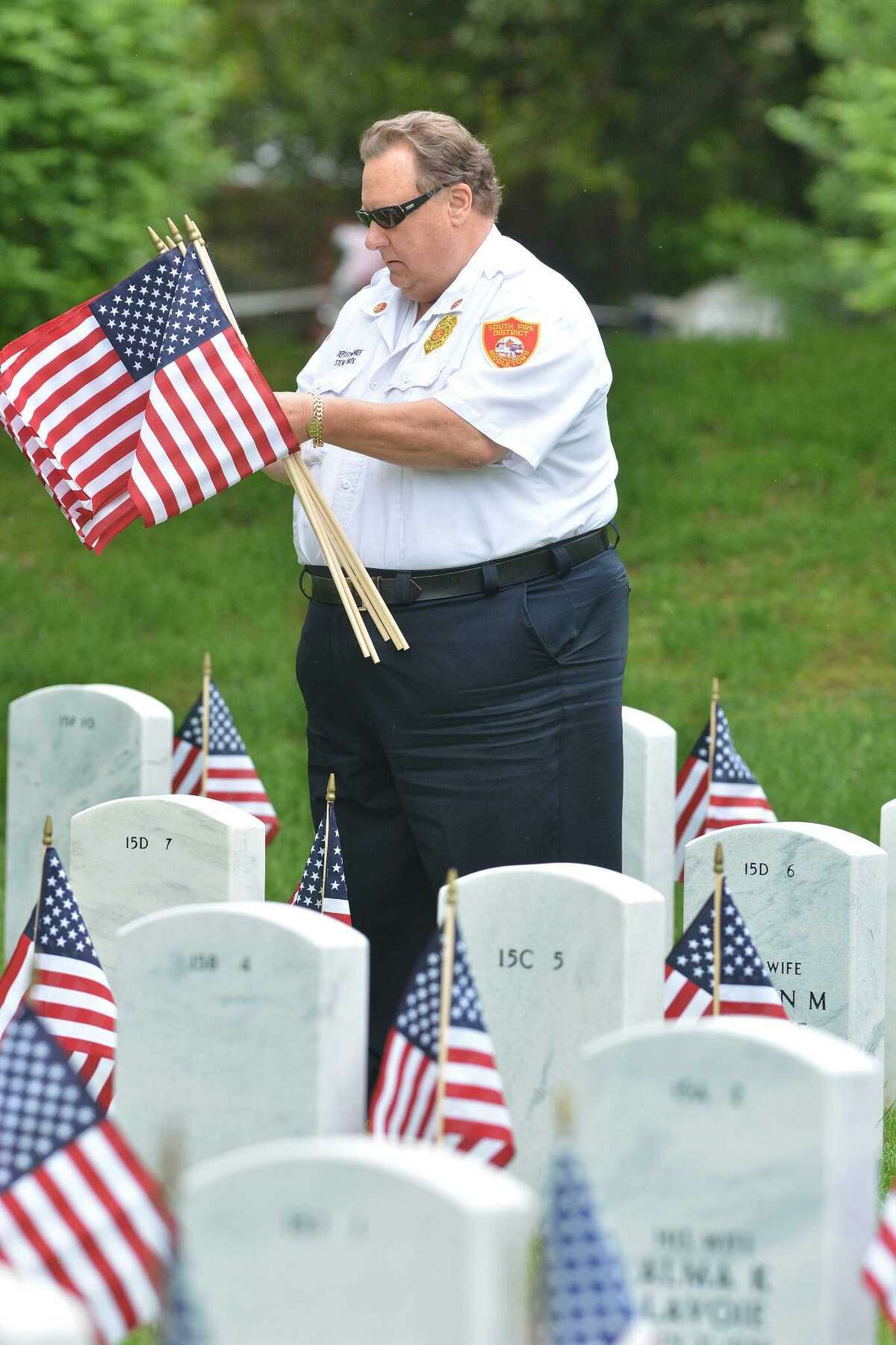 Deputy Chief and Fire Marshal Steven Krol joined of the South Fire District to help local veterans place American Flags at over 6,000 headstones at the Connecticut State Veterans Cemetery at 317 Bow Lane in Middletown on May 23, 2014.