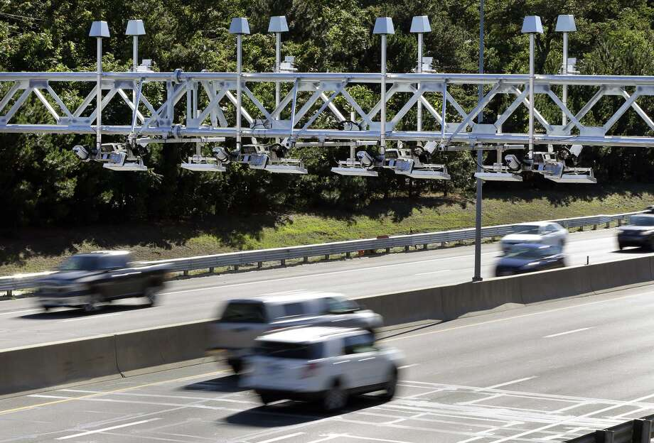 Cars pass under toll sensor gantries hanging over the Massachusetts Turnpike in Newton, Mass., in 2016. Connecticut will be debating tolls, again, this General Assembly session. Photo: AP Photo /Elise Amendola / AP / AP