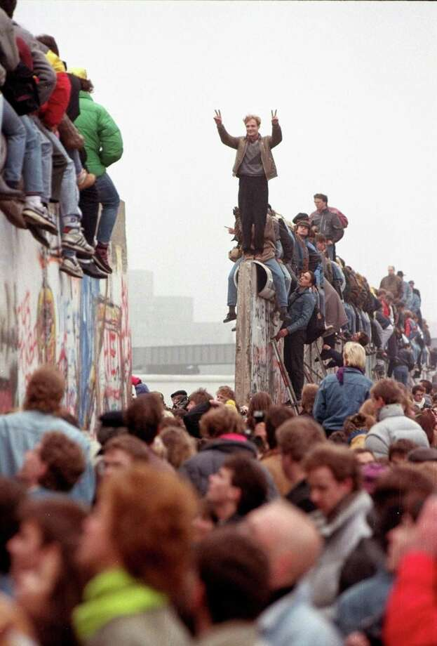 This Nov. 12, 1989 photo shows Berliners celebrating on top of the wall as East Germans flood through the dismantled Berlin Wall into West Berlin at Potsdamer. A reader finds it ironic Americans want to build a wall, when the U.S. cheered for the demolision of the Berlin Wall in the late '80s. Photo: LIONEL CIRONNEAU /AP / AP