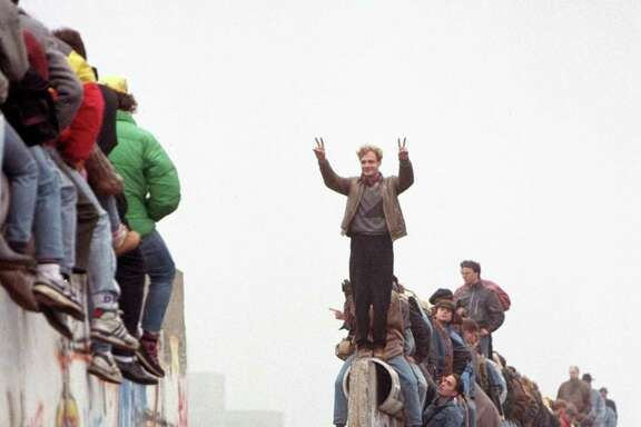 This Nov. 12, 1989 photo shows Berliners celebrating on top of the wall as East Germans flood through the dismantled Berlin Wall into West Berlin at Potsdamer. A reader finds it ironic Americans want to build a wall, when the U.S. cheered for the demolision of the Berlin Wall in the late '80s.