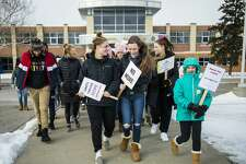Midland High students, along with members of WOMAN (Women of Michigan Action Network), MHS staff and community members walk outside during a One Billion Rising event in support of women across the globe who suffer domestic abuse on Friday, Feb. 15, 2019. (Katy Kildee/kkildee@mdn.net)