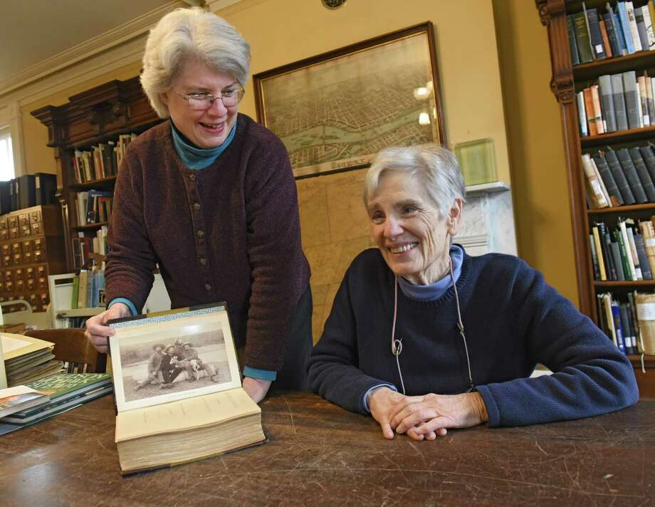"""Curator Stacy Pomeroy Draper, holds the book """"Sport Among the Rockies"""" by The Scribe while retired research librarian Elsa Prigozy, right, is interviewed at Rensselaer County Historical Society on Friday Feb. 15, 2019 in Troy, N.Y. The 78-year-old Prigozy helped to identify men in the limited edition 19th century travel book. (Lori Van Buren/Times Union) Photo: Lori Van Buren, Albany Times Union / 20046159A"""