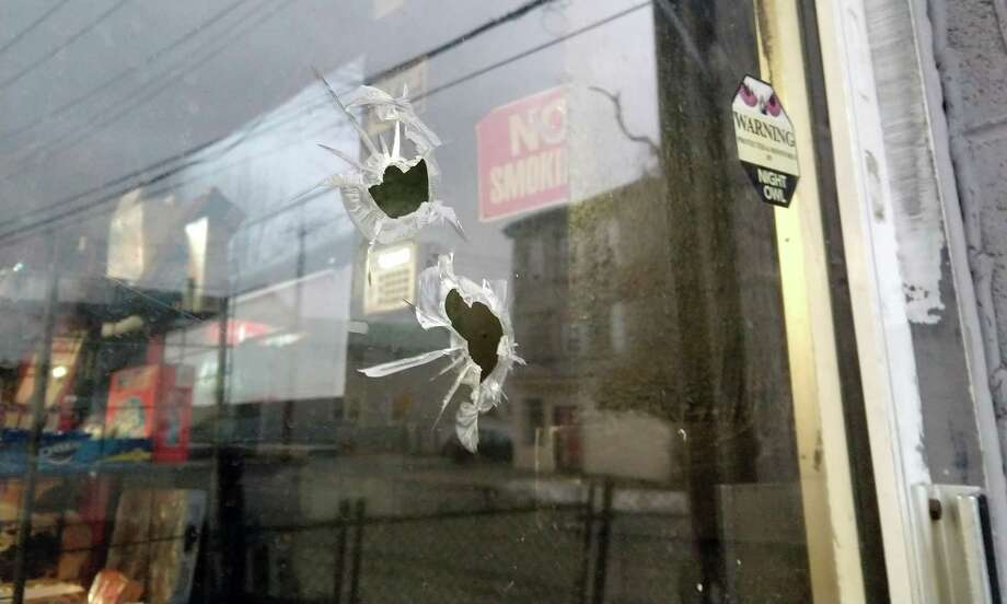 Bullet holes identified by a worker at the Snack Shop, where a customer was shot and killed Tuesday, Jan.16, 2018 in Bridgeport, Conn. It was the city's first homicide of the year. Photo: Cedar Attanasio / Hearst Connecticut Media / Connecticut Post