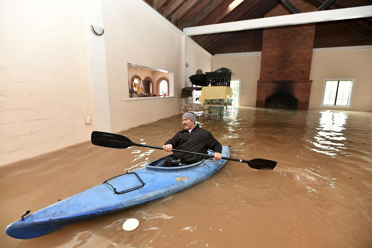 Jay Michael Tucker kayaks through the flooded Surrey Resort as the Russian River flows through it in Guerneville, Calif., Friday, Feb. 15, 2019. Streets and low-lying areas flooded as the Russian River swelled above its banks today. (AP Photo/Josh Edelson)