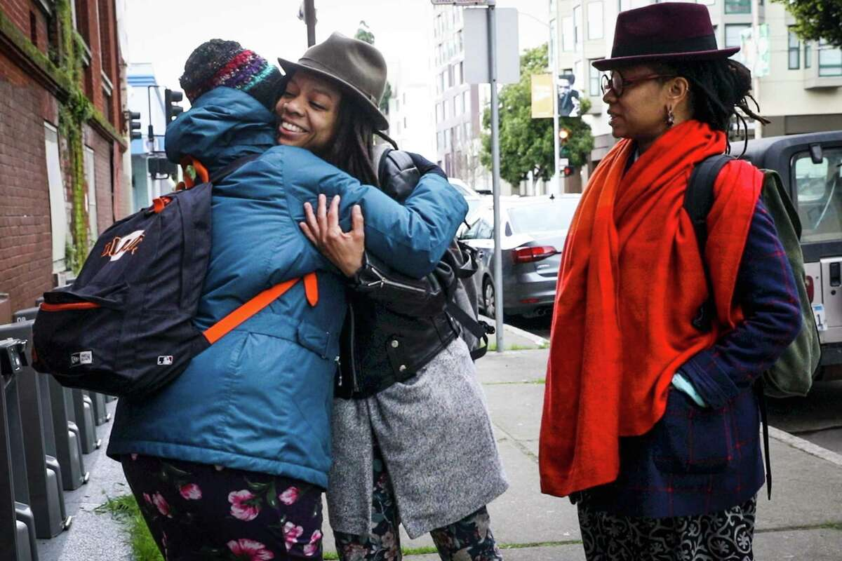 Melonie Green (second from left) hugs a friend as she and Melorra Green head to work.
