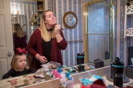 Lindsey McFarland puts on makeup while Lincoln, 2, looks on as they prepare to go to church.