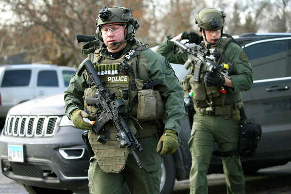 Police officers armed with rifles gather at the scene where an active shooter was reported in Aurora on Friday. Antonio Perez | Chicago Tribune (AP)