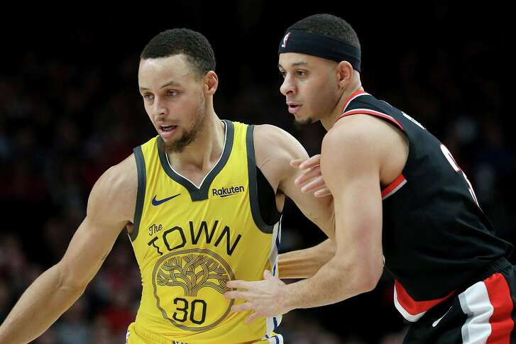 Stephen Curry #30 of the Golden State Warriors and Seth Curry #31 of the Portland Trail Blazers fight for the ball in the second half during their game at Moda Center on February 13, 2019 in Portland, Oregon.