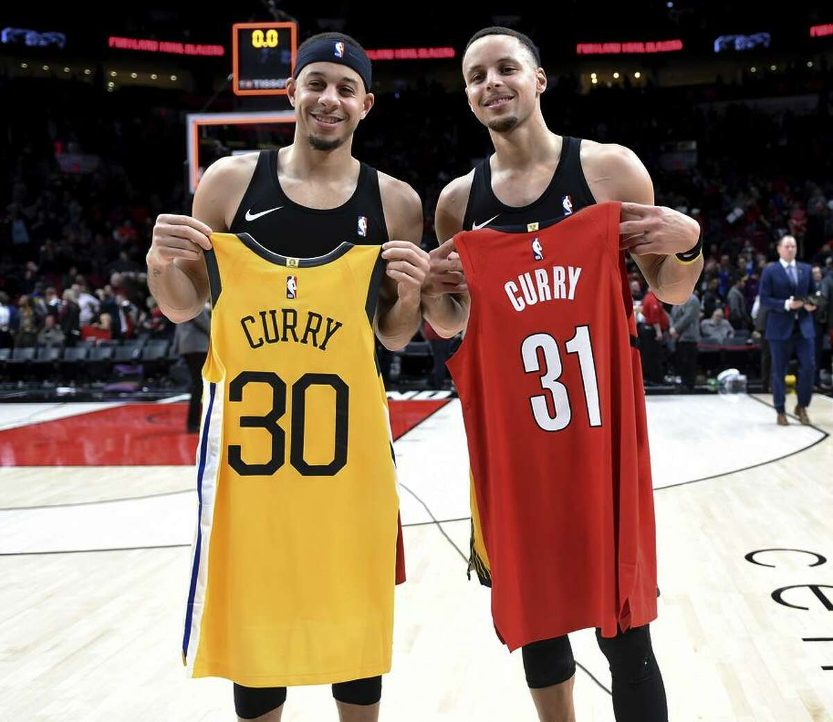 Trail Blazers guard Seth Curry (left) and his brother, Warriors guard Stephen Curry, swap jerseys after a game in Portland.