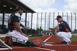 Houston Astros catcher Robinson Chirinos, left, has a one-on-one session with manager AJ Hinch, who used to play cather, at Fitteam Ballpark of The Palm Beaches on Day 1 of spring training on Thursday, Feb. 14, 2019, in West Palm Beach.