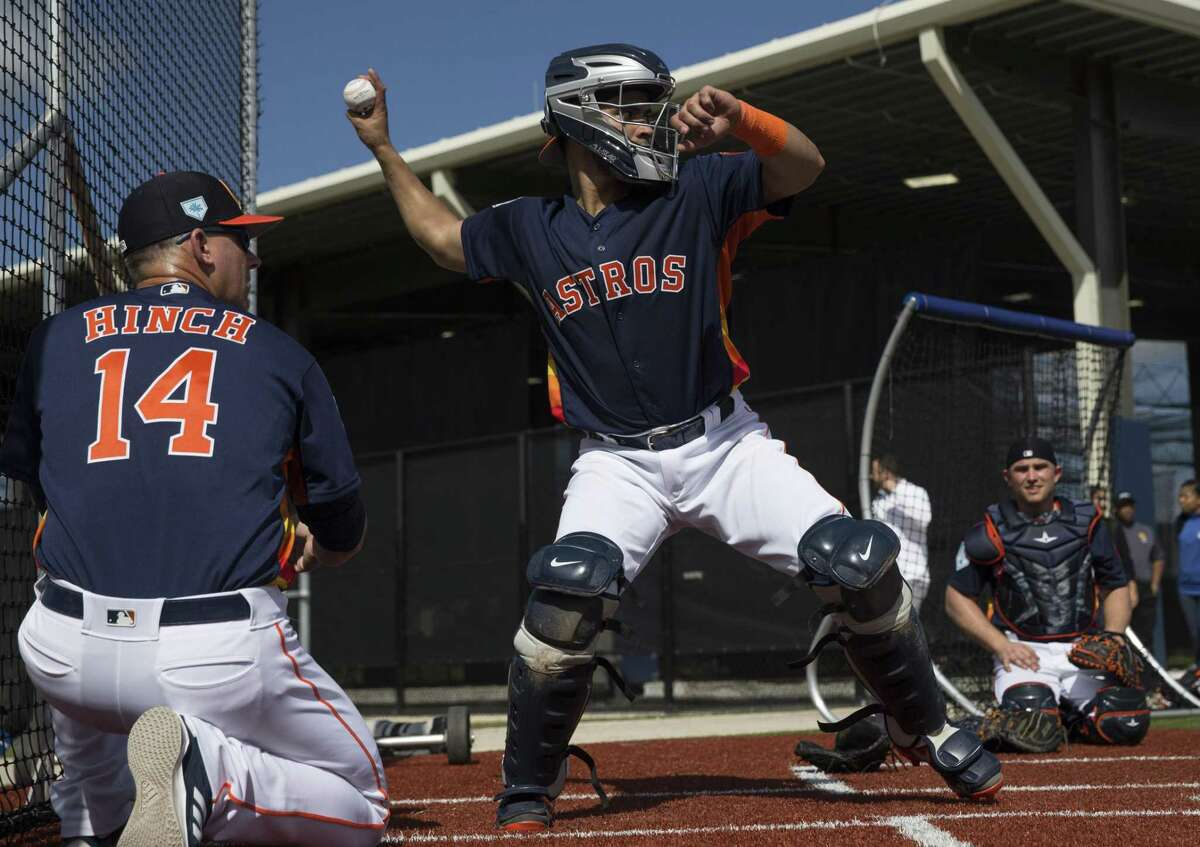 Houston Astros manager AJ Hinch (14) coaches catcher Robinson Chirinos throwing the ball to second base at Fitteam Ballpark of The Palm Beaches on Day 2 of spring training on Friday, Feb. 15, 2019, in West Palm Beach.