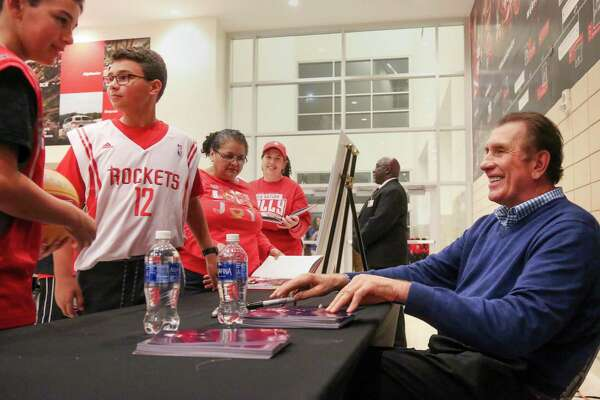 Former Rockets Head Coach Rudy Tomjanovich, right, smiles as he talks with Niko Howard, 11, left, and his brother Ben Howard, 12, second from left, as he signs autographs for fans before an NBA game, at the Toyota Center, Friday, Dec. 16, 2016, in Houston. ( Jon Shapley / Houston Chronicle )