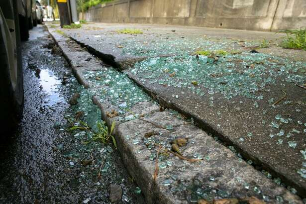 Glass litters the sidewalk from a car break-in near the curvy stretch of Lombard Street, a popular location for burglaries.