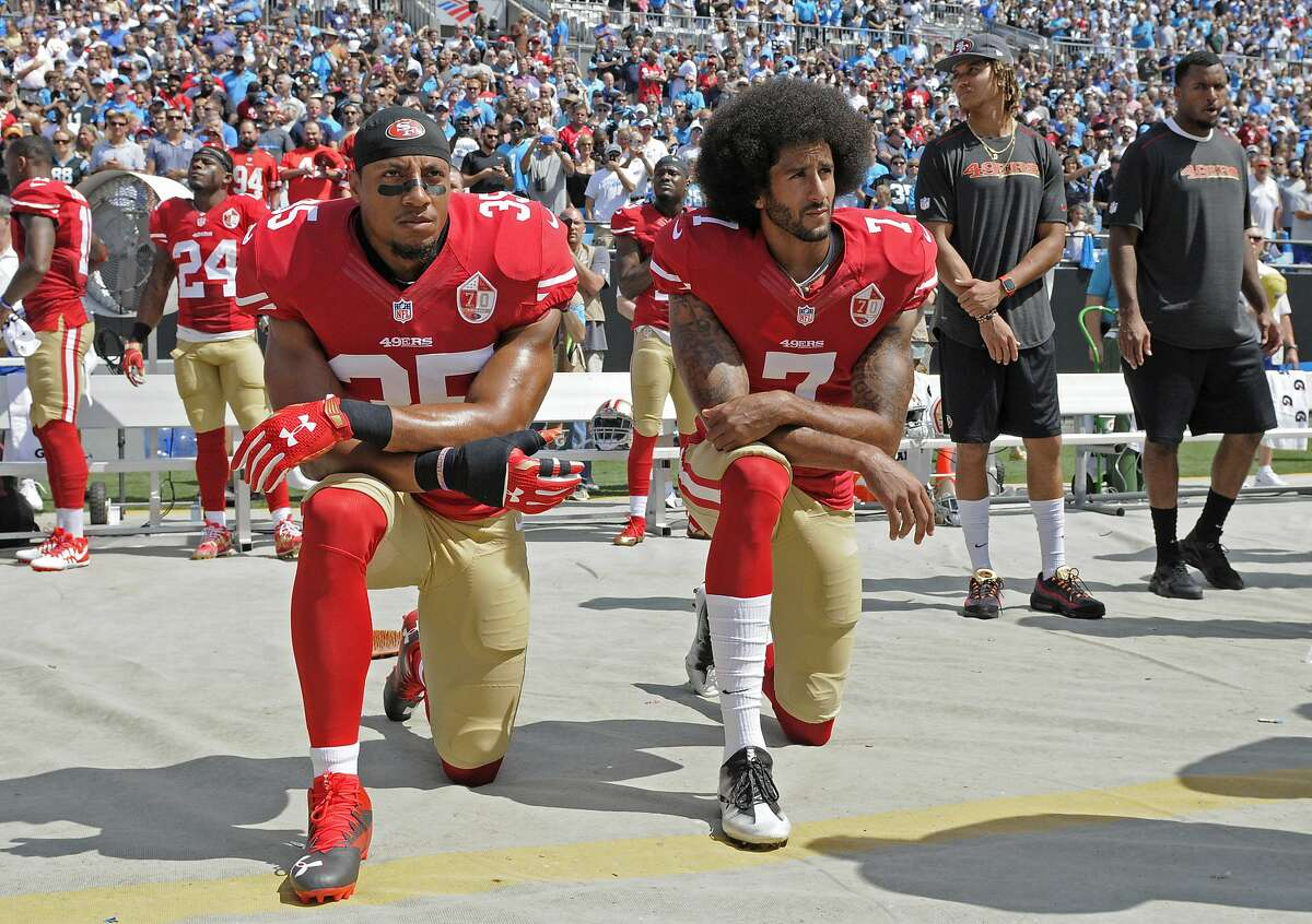 FILE - In this Sept. 18, 2016, file photo, San Francisco 49ers' Colin Kaepernick (7) and Eric Reid (35) kneel during the national anthem before an NFL football game against the Carolina Panthers, in Charlotte, N.C. Colin Kaepernick and Eric Reid have reached settlements on their collusion lawsuits against the NFL, the league said Friday, Feb. 19, 2019. (AP Photo/Mike McCarn, File)