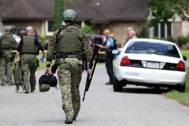 A SWAT team member walks down the street during a standoff at 20331 Belleau Wood, Tuesday, Aug. 6, 2013, in Humble. A woman called neighbors to check the welfare of her estranged husband, who ran into his house and threatened suicide for several hours until SWAT team members got him to come out of the house without shots being fired. No charges were brought against the man. ( Karen Warren / Houston Chronicle )