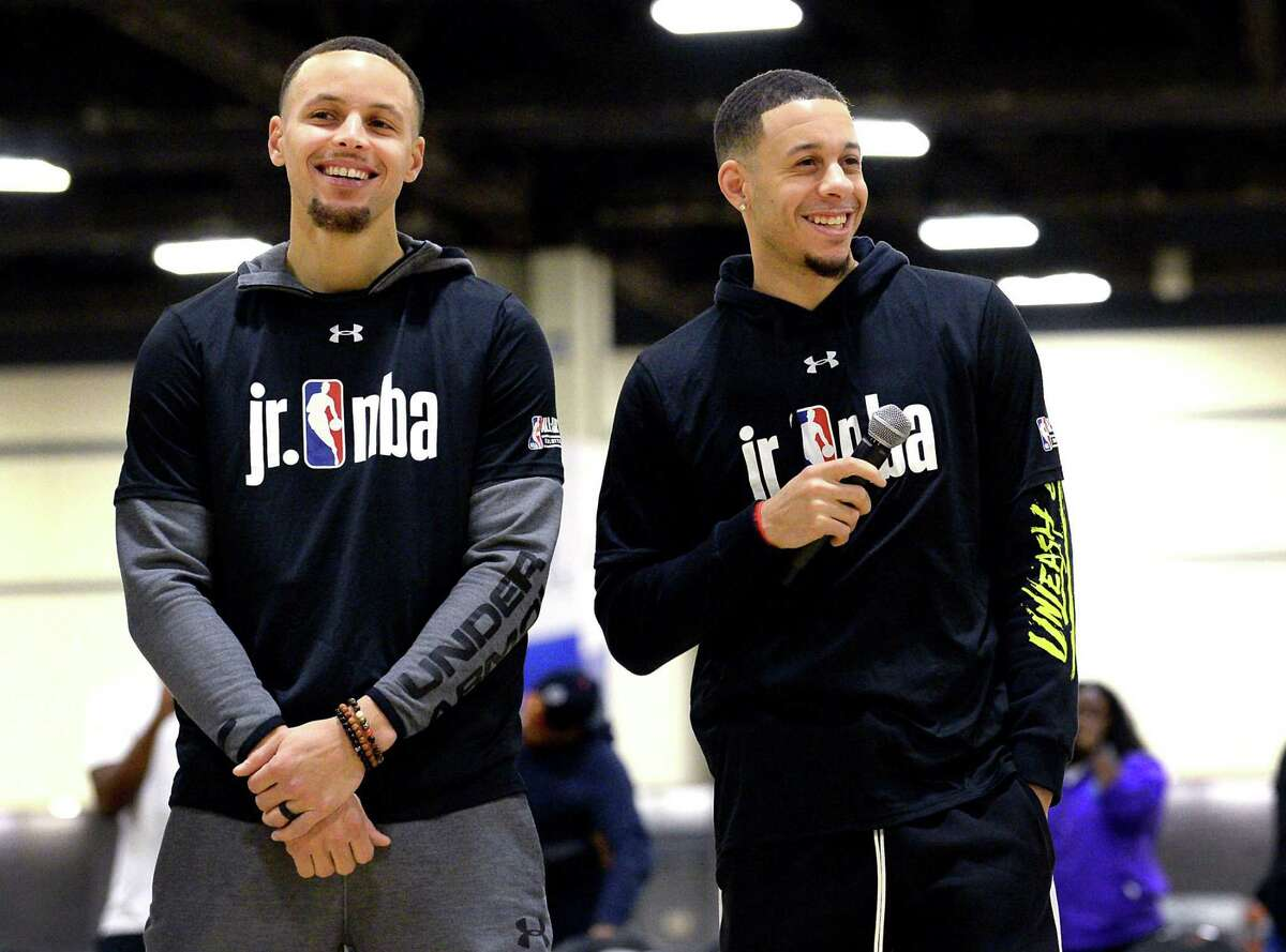 Stephen Curry, left, smiles as his brother, Seth Curry, addresses students during Jr. NBA Day in Charlotte, N.C.