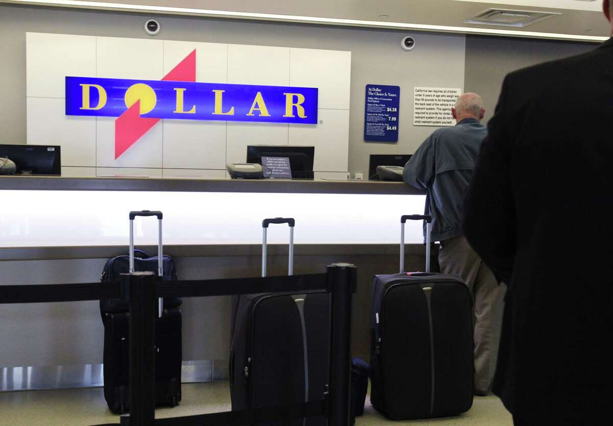 Customers wait in line at a Dollar rental car counter at San Jose International Airport.