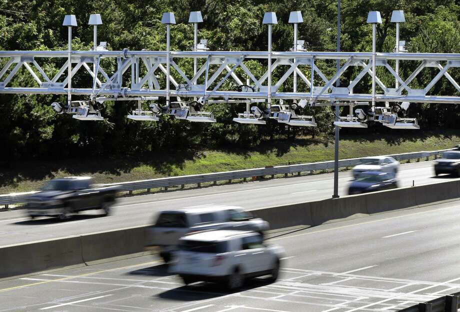 Cars pass under toll sensor gantries hanging over the Massachusetts Turnpike in Newton, Mass. in 2016. The Connecticut General Assembly will be debating the installation of tolls this session. Photo: Elise Amendola / Associated Press / AP