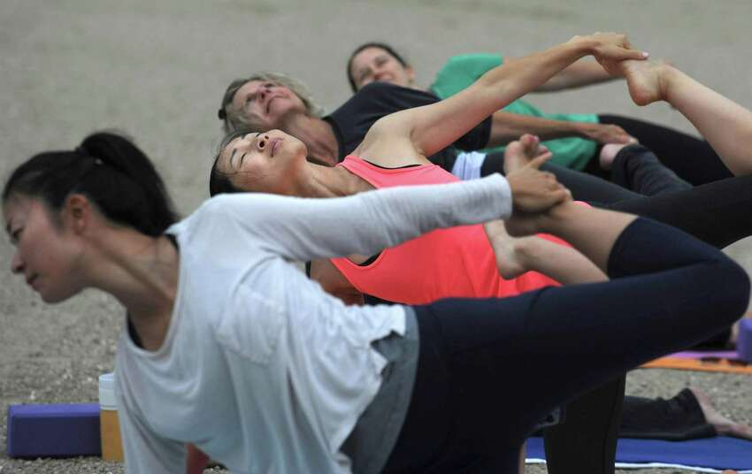 Ye Feng, second from left, attends Community Yoga at Bayley Beach, in their 6th season, Saturday, August 4, 2018, in Rowayton, Conn. The classes, sponsored by the Sixth Taxing District, begin Memorial Day Weekend each year and run through September 30. Weekend classes start at 8am. Thursday classes start at 9:15am.