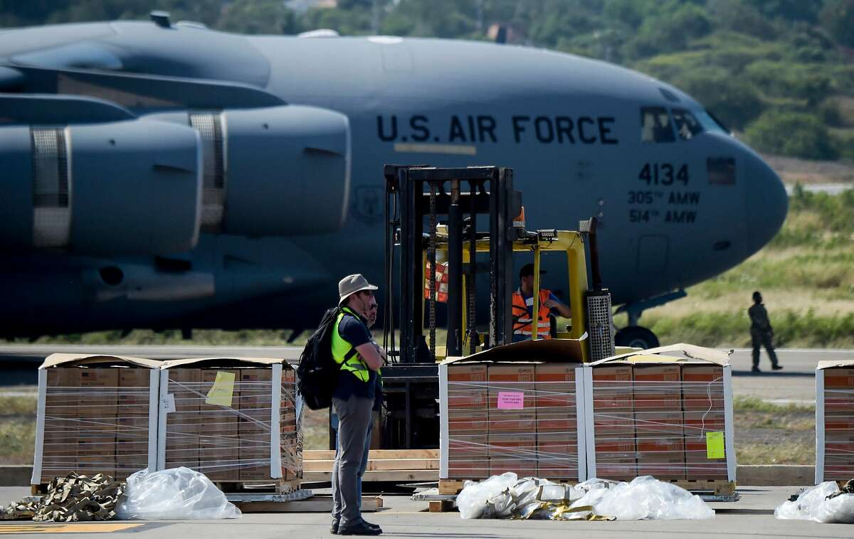"""Food and medicine aid for Venezuela is unloaded from a US Air Force C-17 aircraft at Camilo Daza International Airport in Cucuta, Colombia in the border with Venezuela on February 16, 2019. - Venezuelan opposition leader Juan Guaido on Saturday called for nationwide protests next week to support volunteers planning to travel to the border with Colombia to bring in US humanitarian aid, the latest flashpoint in the country's political crisis. The announcement came as tons of US food aid was piling up along the border. It has been denounced by President Nicolas Maduro, who has asked the military to reinforce the frontier, denouncing the food as a """"booby trap"""" and a cover, he said, for a planned US military invasion. (Photo by Raul ARBOLEDA / AFP)RAUL ARBOLEDA/AFP/Getty Images"""