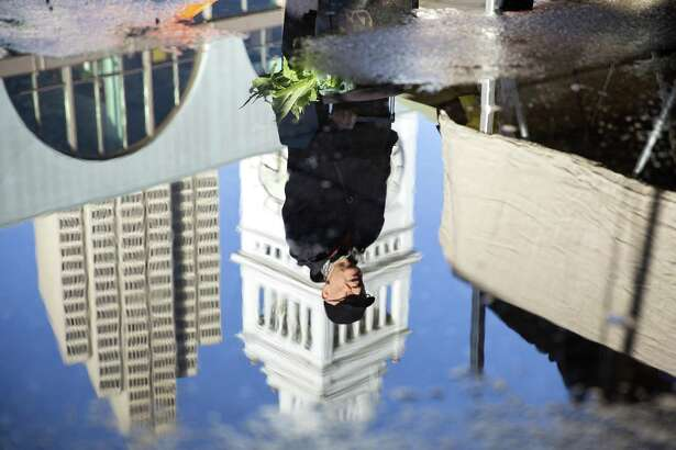 A man is reflected in a puddle at the Ferry Plaza Farmers Market in San Francisco.