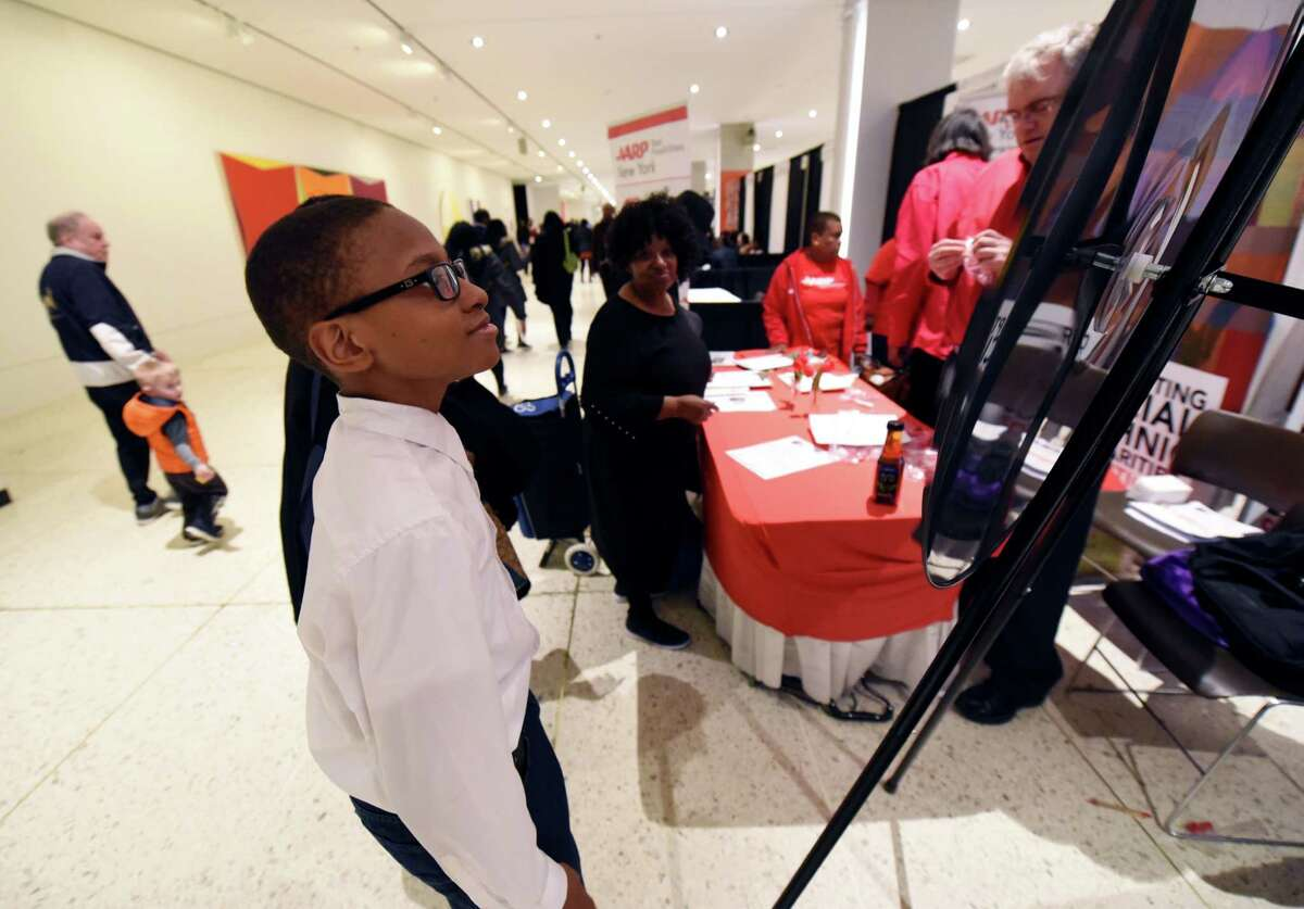 Quadir Lovell, 14, spins a wheel to win a prize at the AARP booth during the New York State Association of Black and Puerto Rican Legislators conference Saturday, Feb. 16, 2019 at the main concourse in Albany, NY. (Phoebe Sheehan/Times Union)