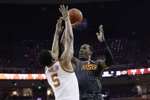 Oklahoma State forward Cameron McGriff, right, shoots over Texas forward Royce Hamm Jr. (5) during the first half of an NCAA college basketball game, Saturday, Feb. 16, 2019, in Austin, Texas. (AP Photo/Eric Gay)