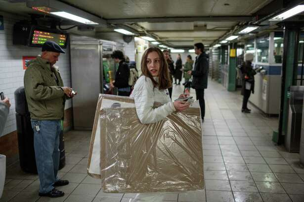 Alexandria commutes on the subway from her apartment on the Upper West Side to the United Nations, holding her protest signs.