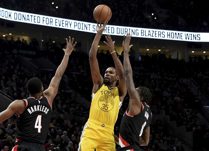 Golden State Warriors forward Kevin Durant, center, hits a shot over Portland Trail Blazers forward Maurice Harkless, left, and forward Al-Farouq Aminu, right, during the first half of an NBA basketball game in Portland, Ore., Wednesday, Feb. 13, 2019. (AP Photo/Steve Dykes)