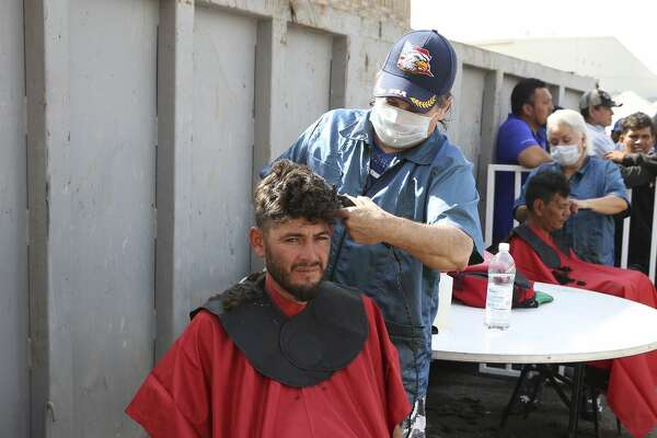 A Central American immigrant gets a haircut at a shelter in Piedras Negras, Mexico, Tuesday, Feb. 5, 2019. The group numbering around 1,800 is at the shelter across the Rio Grande from Eagle Pass, Texas.