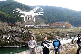Drones fly against a scenic backdrop in Naka, Japan.