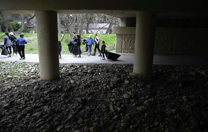 Volunteers walk the West Avenue overpass as individuals and organizations spanned out across the city's waterways to collect trash and debris for the city's annual Basura Bash on Saturday, Feb. 16, 2019. Some of the 2,000 volunteers went to Walker Ranch Park on the city's North Central side and picked up debris from the Salado Creek Greenway. Volunteers and Parks and Recreation employees joined forces in the cleanup effort. Last year, volunteers collected more than 27 tons of trash, nearly two tons of metal and 259 tires. (Kin Man Hui/San Antonio Express-News)