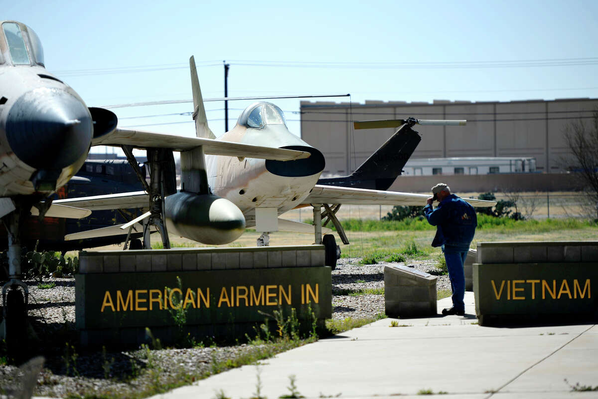 A man reads a plaque at a memorial commemorating the aircraft of the Vietnam War and the pilots who flew them, Feb. 16, 2019 at the CAF Airpower Museum in Midland. Aircraft pictured foreground to background, F-105 Thunderchief, and F-100 Super Sabre. The tail rotor of a UH-1 Huey helicopter is visible in the background. James Durbin/Reporter-Telegram