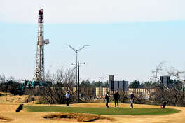 Competitiors in a high school golf tournament play a green in the vicinity of a Trinidad drilling rig Feb. 16, 2019 at Hogan Park Golf Course in Midland. James Durbin/Reporter-Telegram