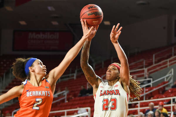 Lamar's Moe Kinard jumps as she takes a shot while Sam Houston's Amber Leggett tries to block her during the game at the Montagne Center on Saturday. Photo taken on Saturday, 02/16/19. Ryan Welch/The Enterprise