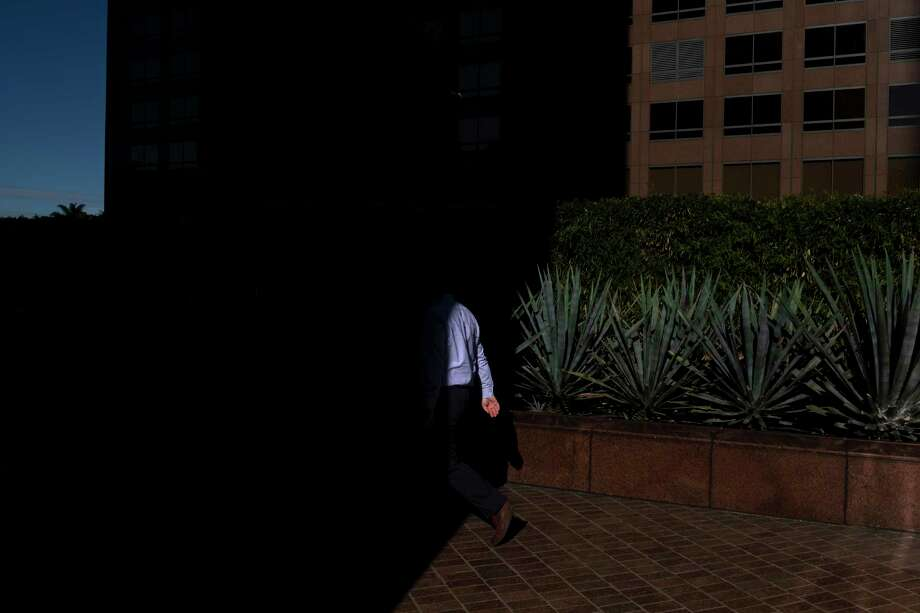 FILE- In this Dec. 4, 2018, file photo a man walks into the shade of a building in downtown Los Angeles. When deciding whether to buy, skip or toss an item, minimalists try to determine whether it adds value to their lives. Apply minimalism to your financial life, and you can shed outdated obligations and reduce stress. (AP Photo/Jae C. Hong, File) Photo: Jae C. Hong / Copyright 2019 The Associated Press. All rights reserved.
