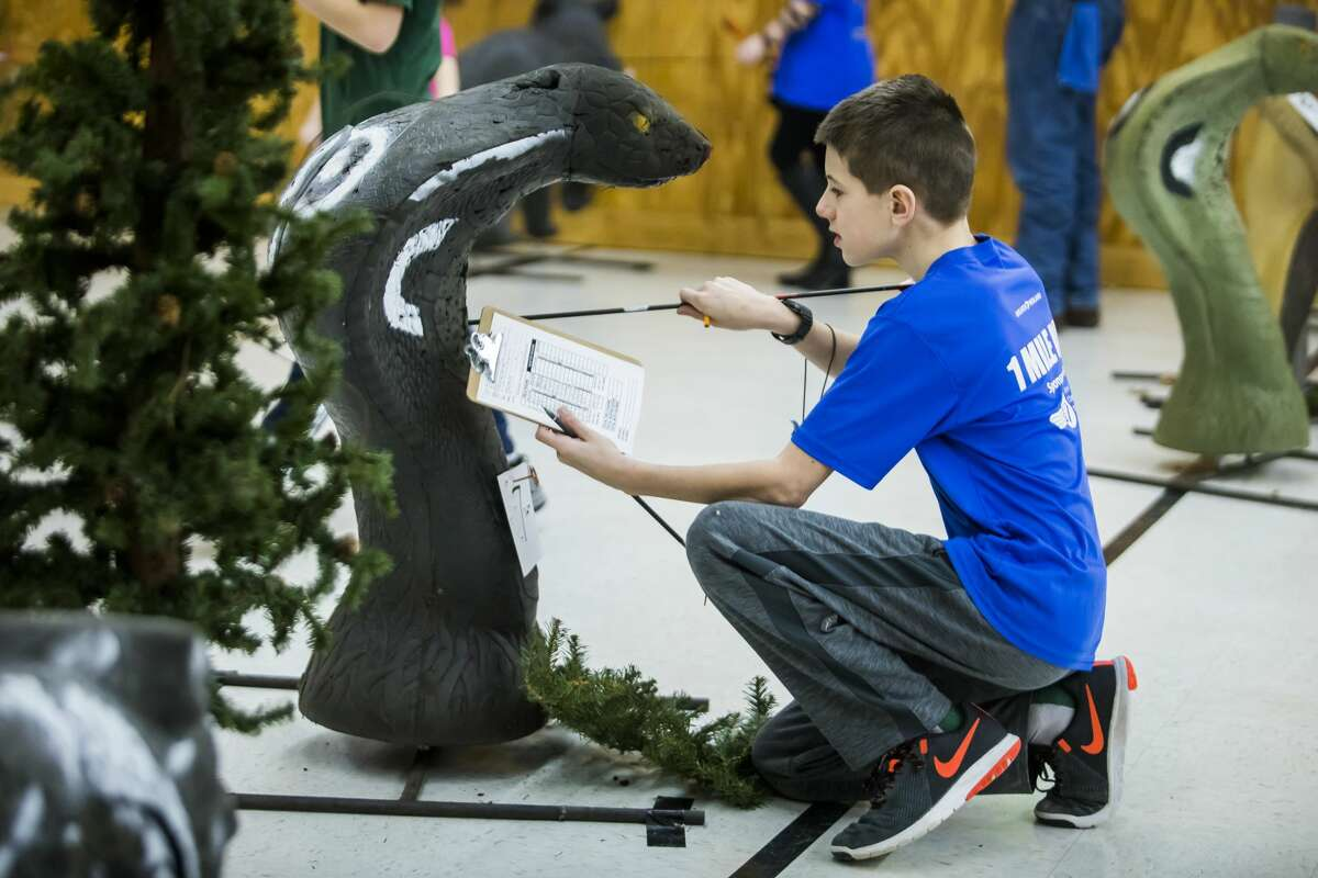 Owen Yankey of Sanford, 10, collects his arrows during a youth archery event on Saturday, Feb. 16, 2019 at Mid Michee Bowmen in Midland. (Katy Kildee/kkildee@mdn.net)