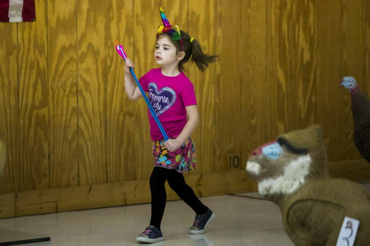 Callie Wilson of Midland, 5, skips after collecting her arrows during a youth archery event on Saturday, Feb. 16, 2019 at Mid Michee Bowmen in Midland. (Katy Kildee/kkildee@mdn.net)
