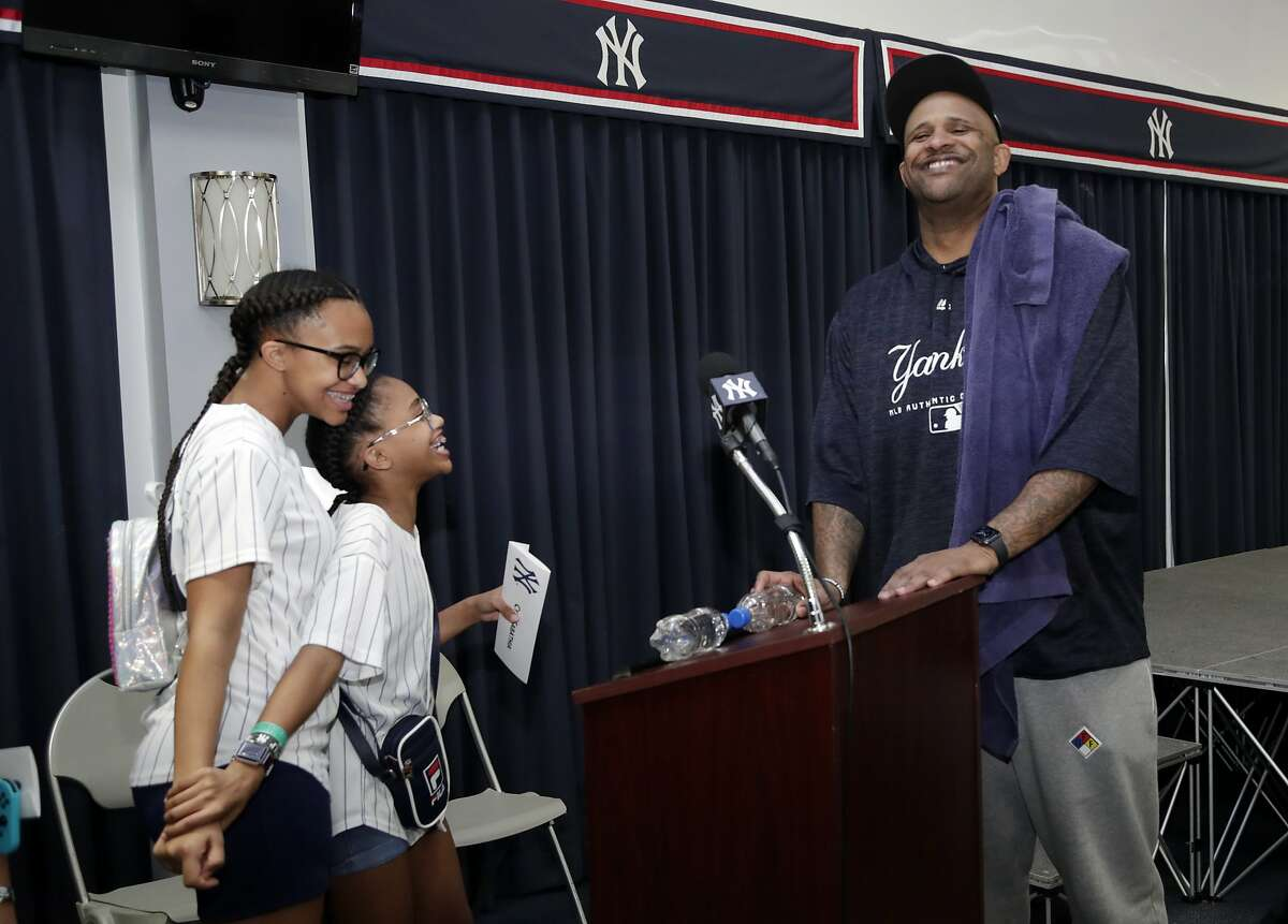 New York Yankees starting pitcher CC Sabathia, right, laughs with his daughters Jaden, left, and Cyia, center, after a news conference at the New York Yankees spring training baseball facility, Saturday, Feb. 16, 2019, in Tampa, Fla. Sabathia announced he will retire after the 2019 season.(AP Photo/Lynne Sladky)