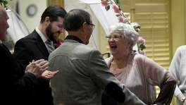 Janice Thompson, 83, reacts after a kiss from her groom, Cardenio Montoya, 89, during their wedding ceremony at Holiday Retirement's Madison Estates on Saturday, Feb. 16, 2019.