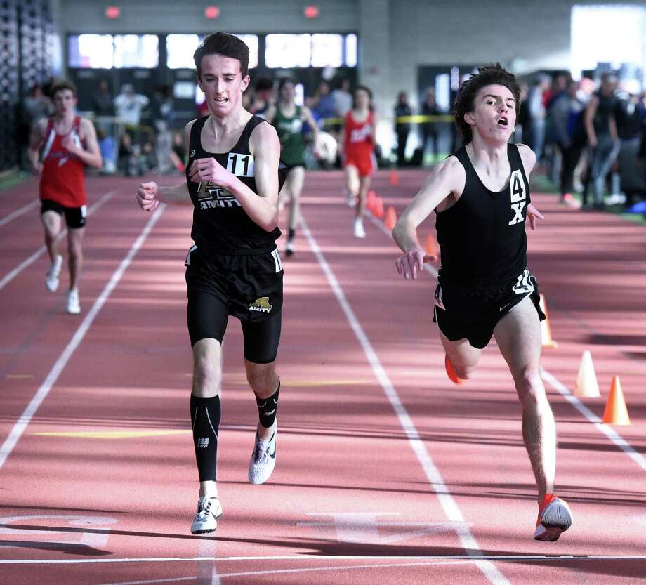 Amity's Connor Visnic, left, is edged out by Xavier's Robbie Cozean at the finish line in the 3,200 at the State Open track championship in February. Photo: Arnold Gold / Hearst Connecticut Media / New Haven Register
