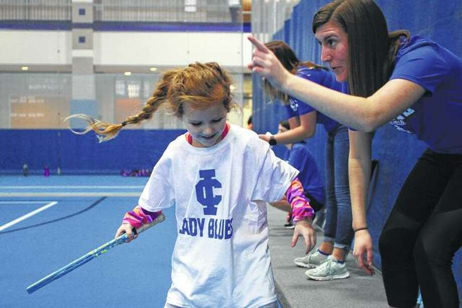 Lauren Cullison practices tennis skills with the help of student athlete Sally Hixon at Saturday's sports skills camp hosted by Illinois College. The camp, in its second year, is part of IC's activities recognizing National Girls and Women in Sports Day. The day-long camp is open to girls in kindergarten through eighth grade. Go to myjournalcourier.com for more photos from the camp. Photo: Rosalind Essig | Journal-Courier