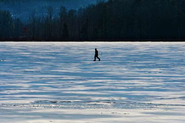 A man makes his way across Round Lake to drill a hole in the ice for fishing on Sunday, Feb. 17, 2019, in Round Lake, N.Y. (Paul Buckowski/Times Union)