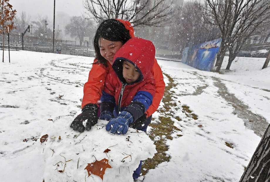 Jinchun Xia (left) and Kevin Liu, of San Francisco, play in the snow Friday at Wingfield Park in Reno. Photo: Andy Barron / Reno Gazette-Journal