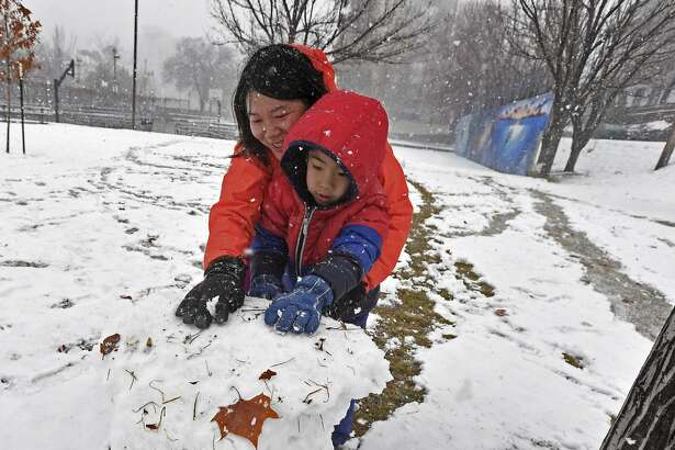 Jinchun Xia, left, and Kevin Liu, 5, of San Francisco, roll a ball of snow for a snowman they made at Wingfield Park in downtown Reno, Nev., Friday, Feb. 15, 2019. (Andy Barron/The Reno Gazette-Journal via AP)