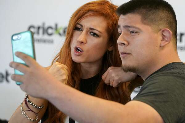 WWE wrestler Becky Lynch, left, makes a video for the sister of fan Thomas Mejia of Houston during an appearance at Cricket Wireless, 8307 Beechnut St., Sunday, Feb. 17, 2019, in Houston.