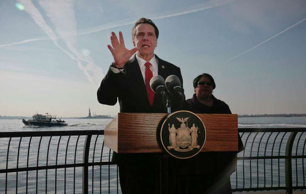 FILE - In this Jan. 21, 2018 file photo, New York Gov. Andrew Cuomo holds a press conference in New York, with the Statue of Liberty and Ellis Island in the distance behind him. The governor will deliver his third inaugural address on New Year's Day at Ellis Island, a site that he says reflects the nation's core principles and one that's likely to stoke speculation that Cuomo may go back on his public statements and run for president.